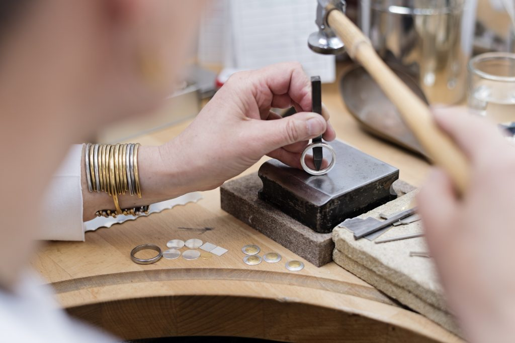Portrait of a professional Goldsmith at work in her workshop creating a silver ring. In this picture she is stamping her hallmark on the inside on the ring. She is surrounded by the tools she uses to create her pieces of jewellery. Colour, horizontal with some copy space.